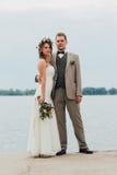 Les jeunes se toilettent et jeune mariée se tenant étreignante sur le fond de la rivière Photo stock
