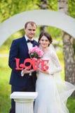 Les jeunes se toilettent, jeune mariée avec le bouquet de mariage et mot d'amour Images stock
