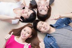 Les jeunes se trouvant sur le plancher Photographie stock libre de droits