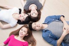 Les jeunes se trouvant sur le plancher Photo stock