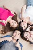 Les jeunes se trouvant sur le plancher Photos stock