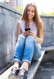 Les jeunes sms des textes de fille d'étudiant et détendent en parc de ville Image stock