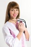 Les jeunes soignent avec le stéthoscope avec ses bras sur le coffre photographie stock libre de droits