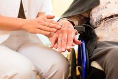 Les jeunes soignent et aîné féminin dans la maison de repos Photographie stock libre de droits
