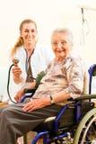 Les jeunes soignent et aîné féminin dans la maison de repos Images libres de droits