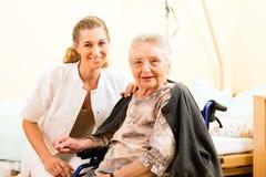 Les jeunes soignent et aîné féminin dans la maison de repos Photos libres de droits