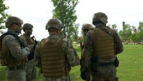 Les jeunes soldats militaires s'assemblent avec des armes discutant un nouveau plan de stratégie pendant l'exercice d'opération banque de vidéos
