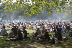Les jeunes sont des chiches-kebabs frits et se reposent en parc local dans Hackney Images stock