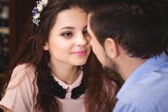 Les jeunes sont enamourés des couples se reposant à une table dans un café et allant à Photos stock