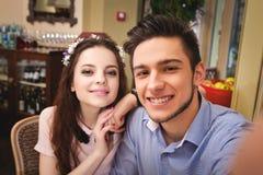 Les jeunes sont enamourés des couples se reposant à une table dans un café et faisant le selfie Image libre de droits