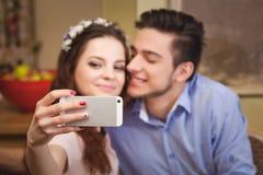 Les jeunes sont enamourés des couples se reposant à une table dans un café et faisant le selfie Photo libre de droits