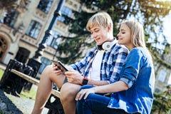 Les jeunes souriant tout en regardant le touchpad dehors photographie stock