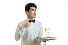Les jeunes sourires avec du charme de serveur corrige le noeud papillon de main et tient un plateau avec des verres de vin Photographie stock