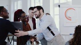 Les jeunes sourires caucasiens de patron, serre la main au collègue africain à l'ÉPOPÉE ROUGE multi-ethnique de mouvement lent de clips vidéos