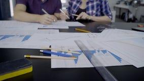 Les jeunes spécialistes écrivent sur des papiers se reposant dans le bureau moderne à l'intérieur banque de vidéos