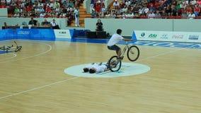 Les jeunes sportifs qualifiés sur des bicyclettes montrent des sauts extrêmes banque de vidéos