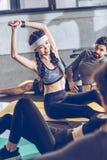 Les jeunes sportifs se reposant et s'étirant sur des tapis de yoga tout en s'exerçant Photo libre de droits