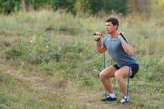 Les jeunes sports musculaires beaux équipent exercer l'extérieur extérieur avec une bande élastique photographie stock