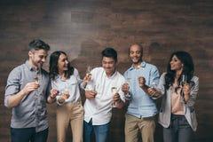 Les jeunes tenant des verres de champagne et de cierges magiques brûlants à l'intérieur Image libre de droits