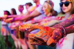 Les jeunes tenant la poudre colorée dans des mains au festival de holi Photographie stock