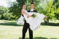 Les jeunes toilettent la jeune mariée de levage dans des bras au jardin Photographie stock