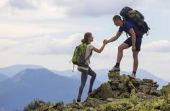 Les jeunes touristes avec des sacs à dos, garçon sportif aide la fille mince à c Images libres de droits