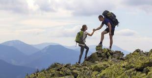 Les jeunes touristes avec des sacs à dos, garçon sportif aide la fille mince à c Image stock