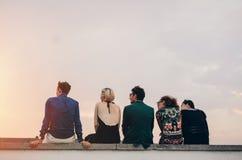 Les jeunes traînant sur le dessus de toit au coucher du soleil Image stock