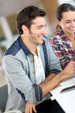 Les jeunes travaillant à l'ordinateur portable et au sourire Photos stock