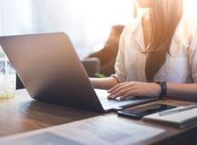 Les jeunes travaillant avec l'ordinateur portable moderne dans le lieu de travail, café photo stock
