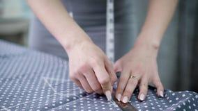 Les jeunes travaillent faire les mesures de tissu avec la bande pour la couture clips vidéos