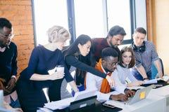 Les jeunes travailleurs ambitieux font le projet d'affaires sur l'ordinateur portable ensemble photos stock