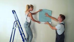 Les jeunes travailleurs de couples au chantier de construction colle le papier peint au mur banque de vidéos