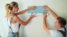 Les jeunes travailleurs de couples au chantier de construction colle le papier peint au mur clips vidéos