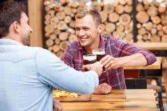 Les jeunes types beaux boivent la bière blonde allemande à grandes gorgées dans la barre Photo stock