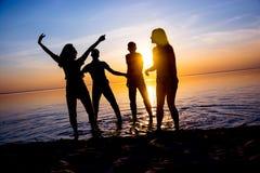 Les jeunes, les types et les filles, étudiantes dansent sur la plage Image libre de droits