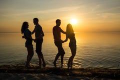 Les jeunes, les types et les filles, étudiantes dansent sur la plage Photo libre de droits