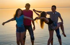 Les jeunes, les types et les filles, étudiantes dansent sur la plage Photographie stock