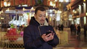 Les jeunes utilisations de type téléphonent en parc d'attractions banque de vidéos