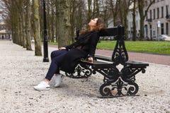 Les jeunes verres noirs reposant le ressort de sourire de femme de portrait de fille de banc de parc d'été enduisent l'automne bo photo stock