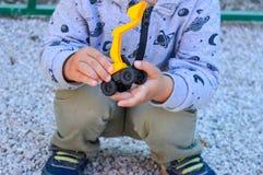 Les jeux d'enfant avec une petite excavatrice de jouet Photographie stock libre de droits