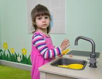 Les jeux de deux ans de fille chez la cuisine des enfants Image libre de droits