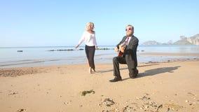 Les jeux de guitariste sur la fille blonde de genou marche autour au lever de soleil banque de vidéos