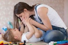 Les jeux de maman avec un petit garçon avec des baisers d'amour rit Photos stock