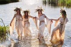 Les jolies femmes avec la guirlande de fleur prennent l'amusement dans l'eau Photos libres de droits