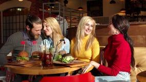 Les jolies filles et le gar?on gai s'asseyant ensemble ? la table et mangent des hamburgers clips vidéos