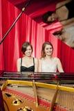 Les jolies filles jouent deux parts d'harmonie sur un piano Photos libres de droits
