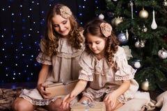 Les jolies soeurs partagent des cadeaux près de Noël Photographie stock libre de droits