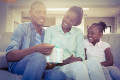 Les jolis couples offrent un présent pour leur fille image stock
