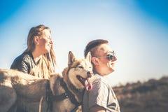 Les jolis couples reposent extérieur dans la forêt avec le chien de traîneau Photographie stock
